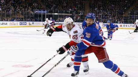 The Rangers' Dominic Moore gets off a shot