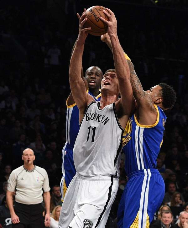 Nets' Brook Lopez is defended under the basket