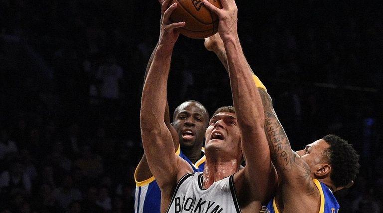 Nets' Brook Lopez is defended under the basket