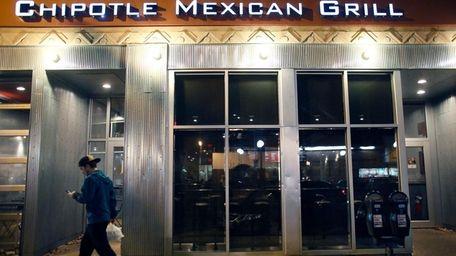 A man walks near a closed Chipotle restaurant
