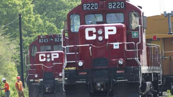 Surveyors work next to Canadian Pacific trains in