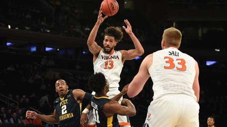 Virginia forward Anthony Gill passes the ball, defended