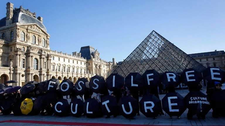 Activists stage a protest outside the Louvre pyramid,