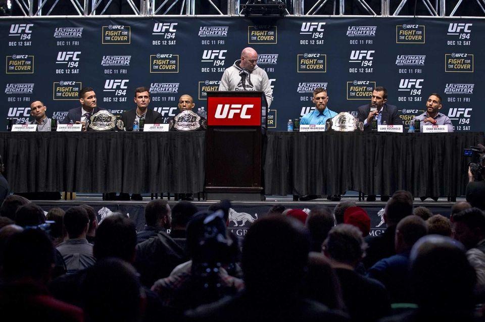 UFC President Dana White, center presides over a