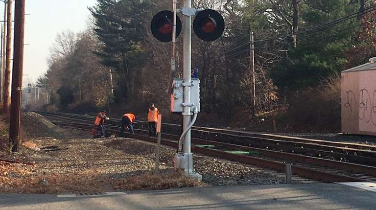 Long Island Rail Road workers inspect the area