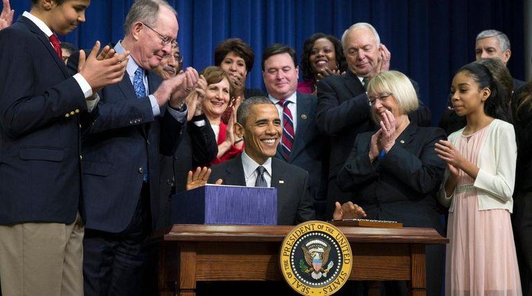 President Barack Obama, center, smiles after signing the