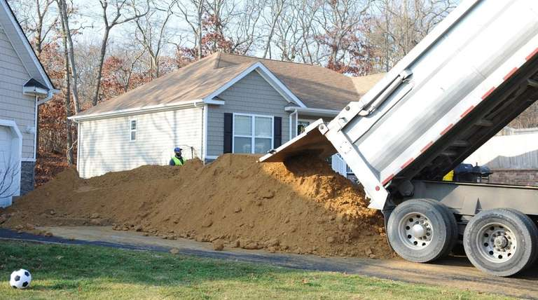 Dirt is unloaded onto the property of homes