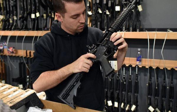 An employee checks the chamber of an assault-style