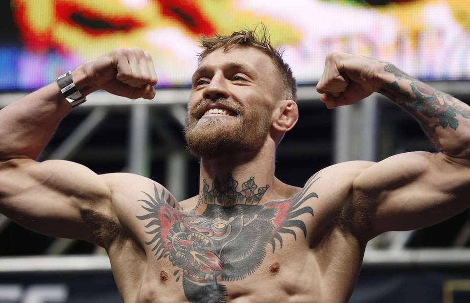 Conor McGregor poses on the scale during the