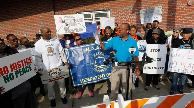 Attorney Frederick Brewington, center, leads a protest outside
