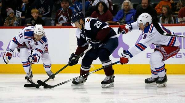 Colorado Avalanche center Nathan MacKinnon, center, loses