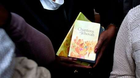 A woman holds books of prayer as she