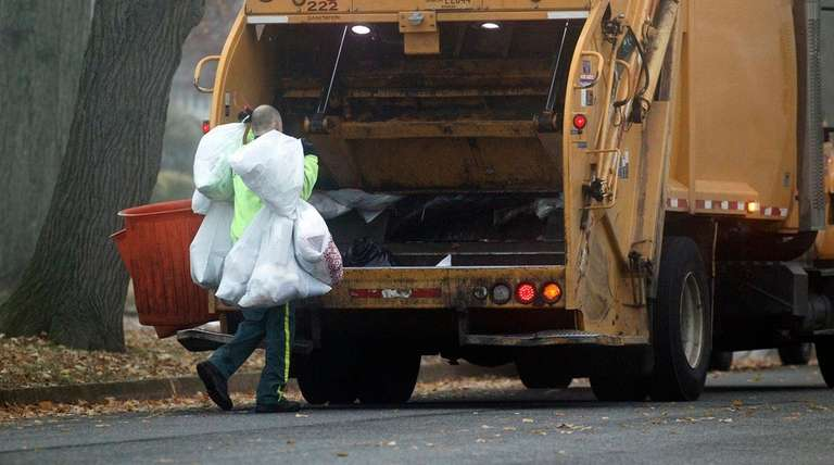 Sanitation workers collect trash on Friday, Dec. 11,