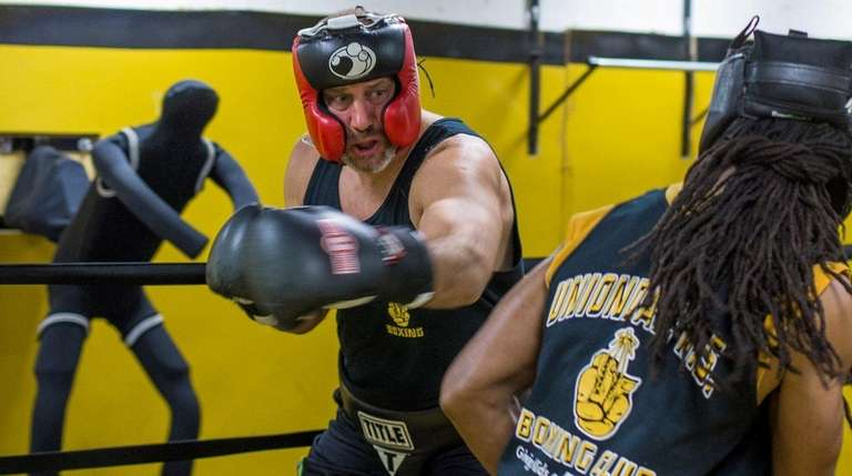 Boxing coach Steven Solomon spars with volunteer coach