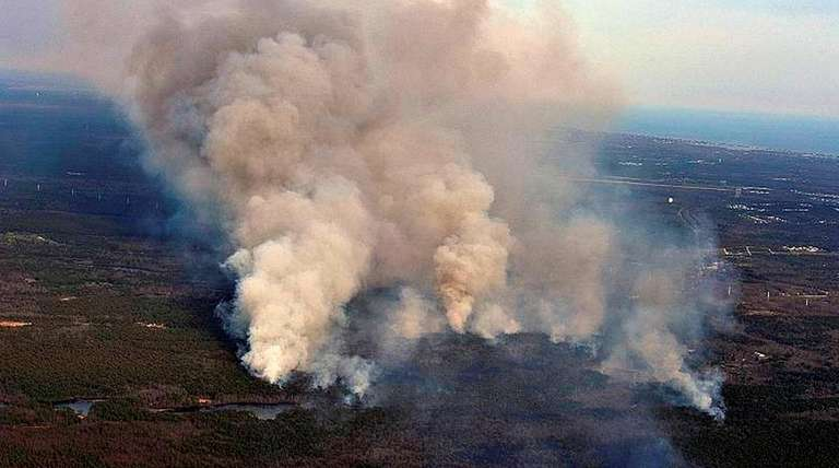 Smoke rises from a massive brush fire in