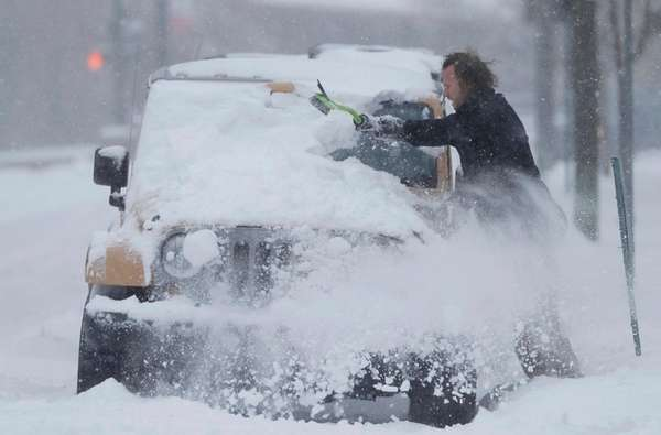An unidentified motorist clears snow off his four-wheel-drive