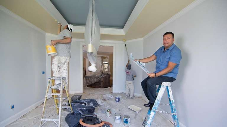 Keith Mazzei works on a dining room in