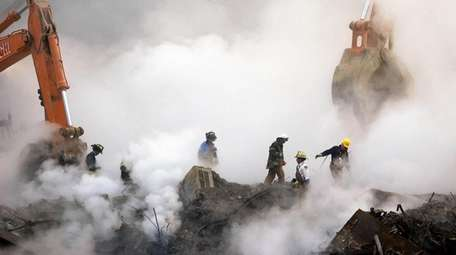 Firefighters make their way over the ruins of