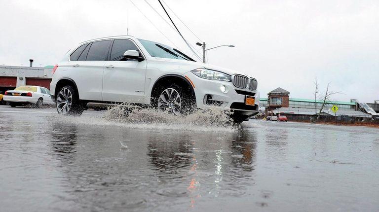 A car navigates a large puddle on Thursday,