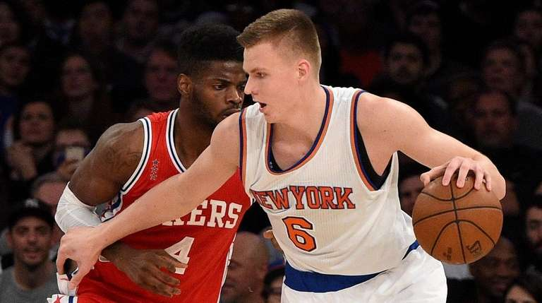 Knicks forward Kristaps Porzingis is defended by 76ers