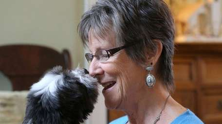 Sue Bohlmann snuggles with one of her dogs,
