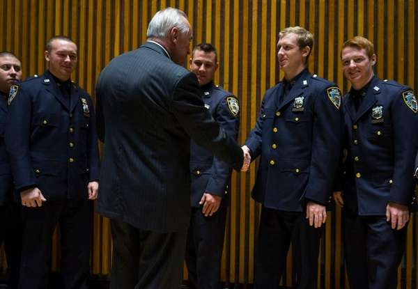 Police Commissioner William Bratton shakes hands with Officer