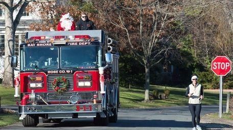 Santa Claus rides around Brightwaters Village in a