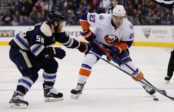 Islanders' Anders Lee carries the puck across the