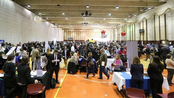 Job seekers speak with prospective employers during