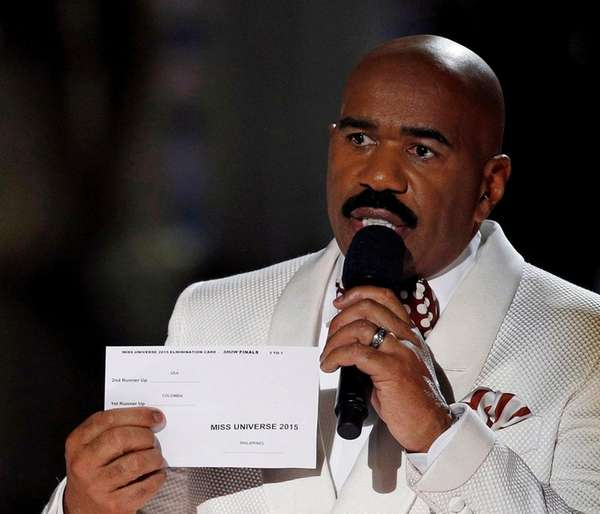 Miss Universe pageant host Steve Harvey holds up