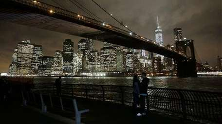 A couple pauses near the Brooklyn Bridge on