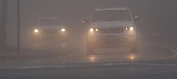 Cars drive in the fog Wednesday morning, Dec.