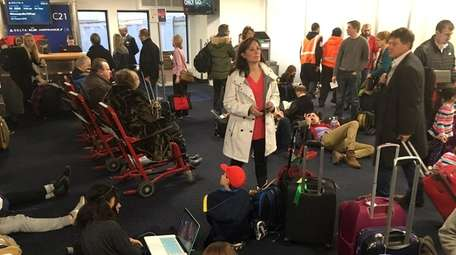 Holiday travelers wait for flights at LaGuardia Airport,