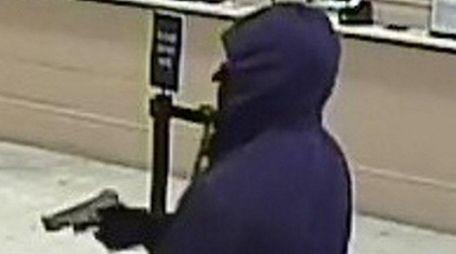 A masked man brandishing a silver automatic handgun