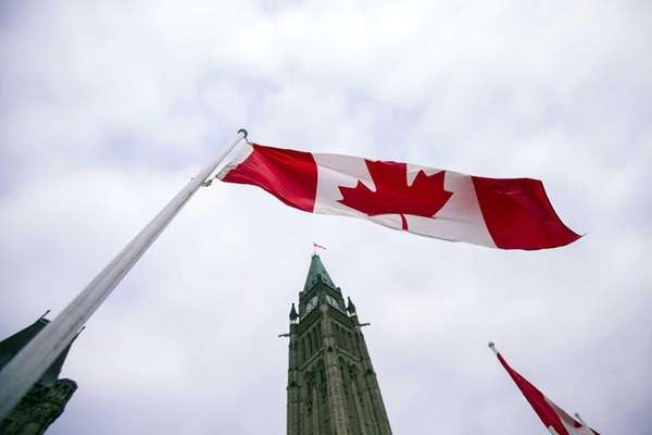 A Canadian flag flies in front of the