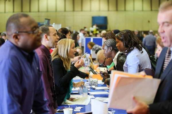 Job seekers speak with prospective employers during the
