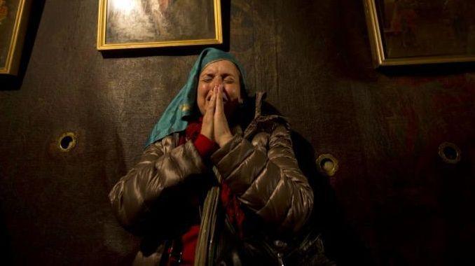 Christian pilgrims pray inside the Grotto of the