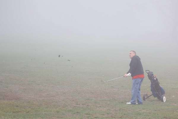 In spite of the fog, a man tries