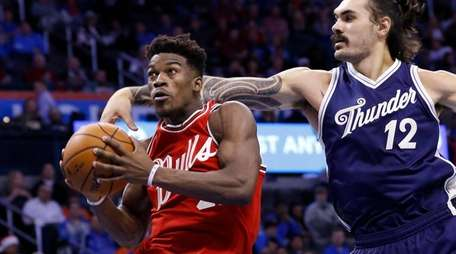 Chicago Bulls guard Jimmy Butler, left, goes to