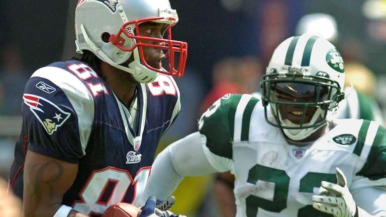 New England Patriots wide receiver Randy Moss,left, catches