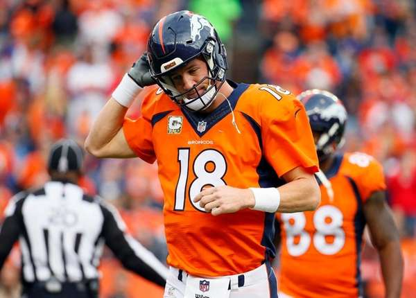 Denver Broncos quarterback Peyton Manning takes off his