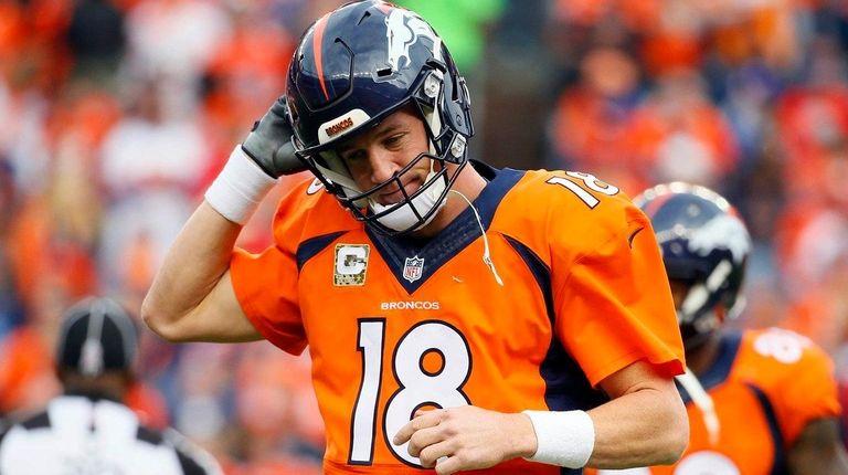 Denver Broncos quarterback Peyton Manning takes off his