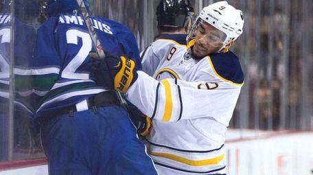 Buffalo Sabres' Evander Kane, right, checks Vancouver Canucks'