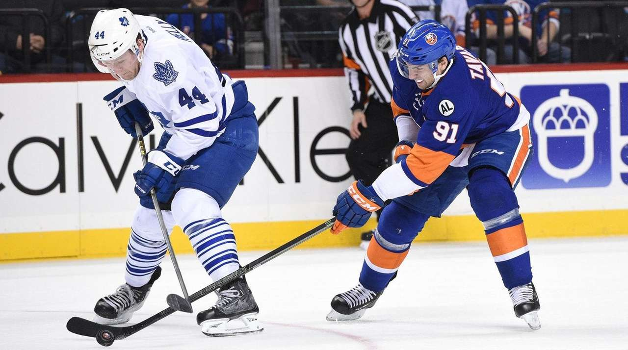 Islanders center John Tavares, right, skates against Maple
