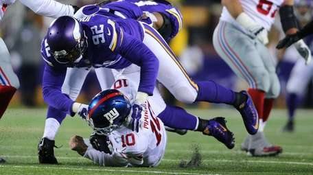 Giants' Eli Manning hits the ground while Vikings'