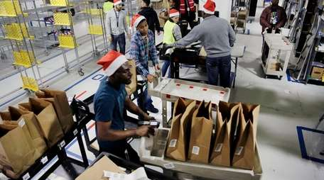 Amazon Prime employees push carts loaded with goods