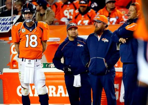 Denver Broncos quarterback Peyton Manning (18) watches from