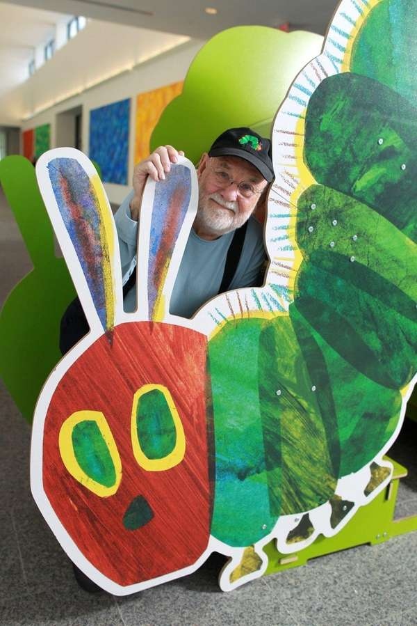 Eric Carle stands with a large cutout of