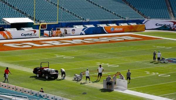 Workers paint the field for the Orange Bowl