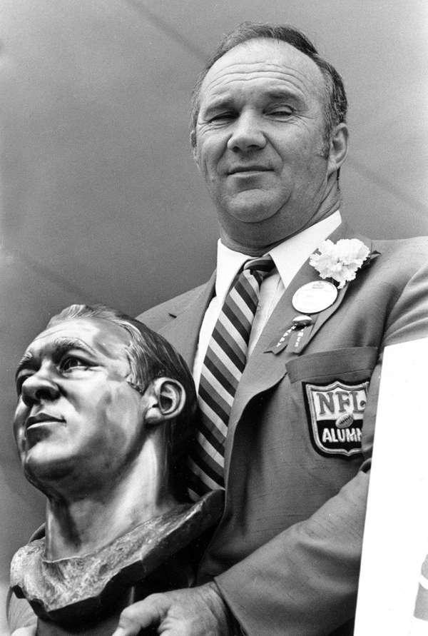 Doug Atkins holds a bust of himself after